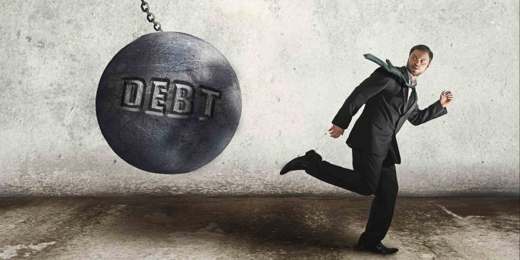 Man running from debt ball swinging on chain