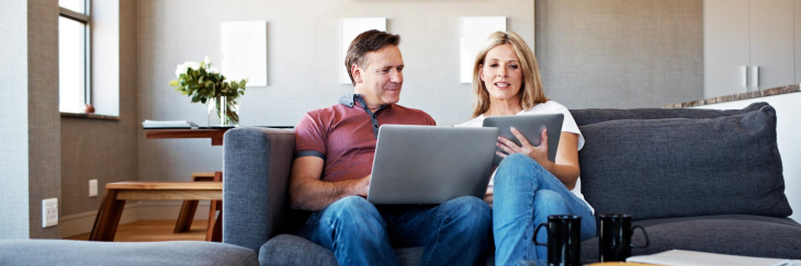 Couple in living room looking at laptop and tablet.