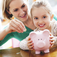 Mother showing child how to save with a piggy-bank.