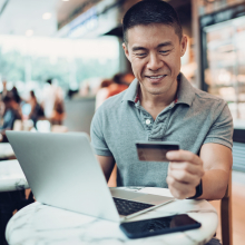 Man Smiling with Credit Card in Cafe