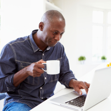 Man online shopping while sipping coffee