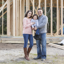 couple and child standing outside of their home construction site