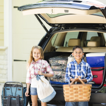 Kids loading up family vehicle for a camping trip